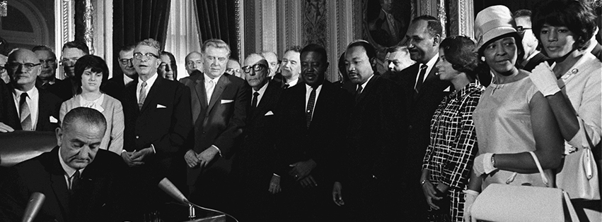 President Lyndon B. Johnson signs the Voting Rights Act of 1965 while Sen. Everett Dirksen, Dr. Martin Luther King, Jr. and others look on.