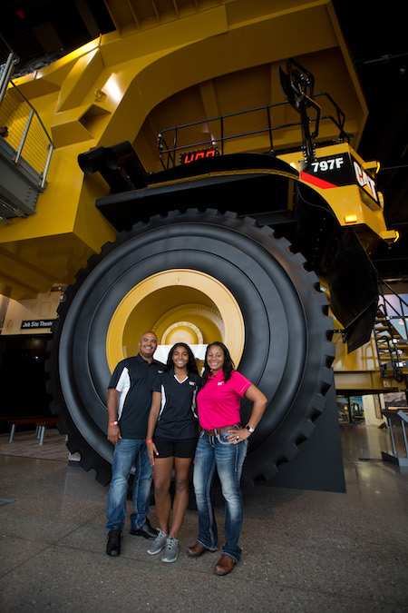 Posing in front of the 14-foot tall Cat® 797 Mining Truck tires.