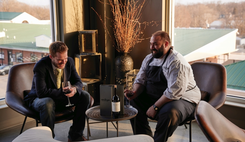 Chef Allen shares a glass of wine with Shane Harvey, at left, who manages the Twelve Bar on the third-floor above Edge.