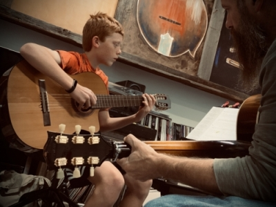 Dave McDonald gives guitar lessons to Calvin Edwards.