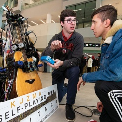 Inventor Michael Kuzma demonstrates his Kuzma Self-Playing Guitar system at an event at Bradley University.