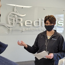 Halley holds a stand-up meeting with a Reditus staff member. Photo by Paul Swiech